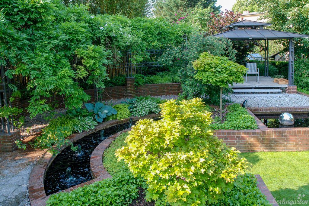 An den Teepavillon schließt sich ein Bereich mit Pergola, Wasserspielen und grünen Blattschmuckstauden an. Das Wasser ist schwarz gefärbt