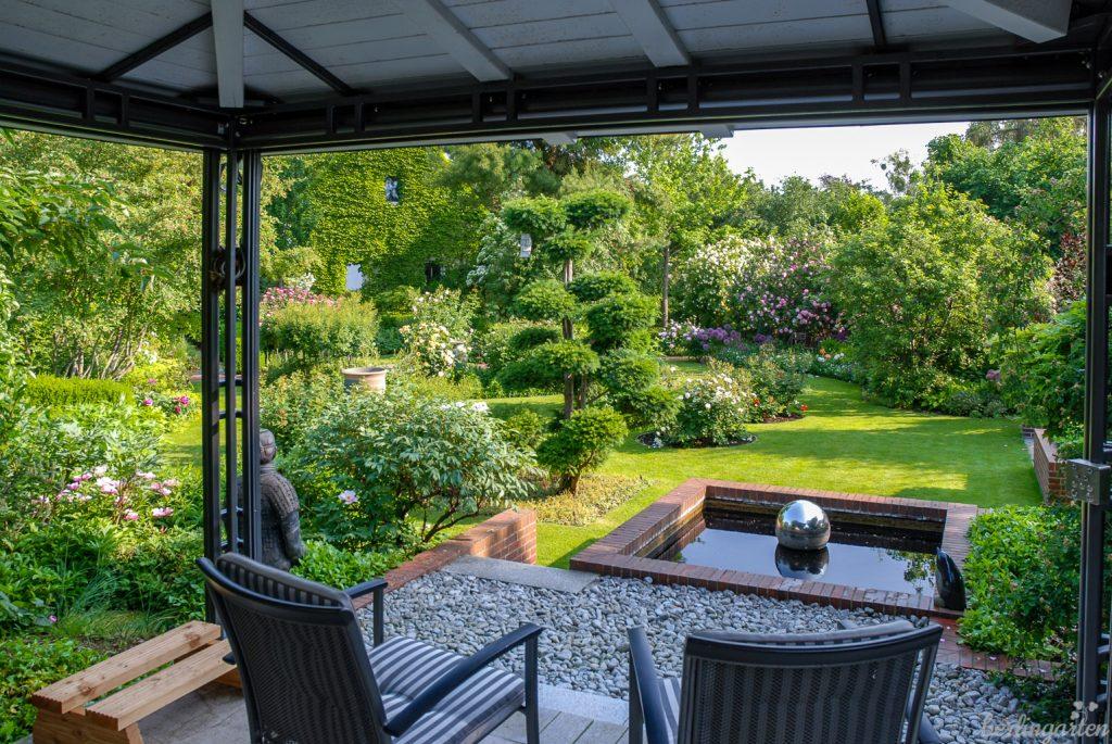 Was für ein schöner Blick vom Pavillon über ein stilles kleines Wasserbecken in den Rosengarten. Im Garten von Rosemary und Rainer wird mit verschiedenen Höhen des Geländes ganz bewusst gespielt